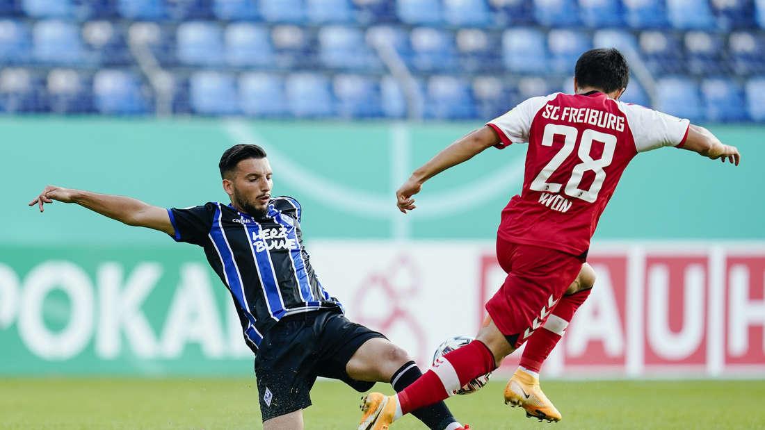 Mannheims Arianit Ferati (l) und Freiburgs Chang-hoon Kwon versuchen an den Ball zu kommen.