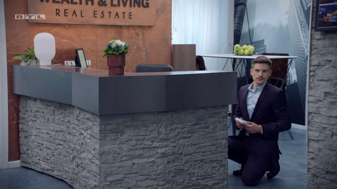 Moritz kniet auf dem Boden vor dem Schrank und schaut sich um