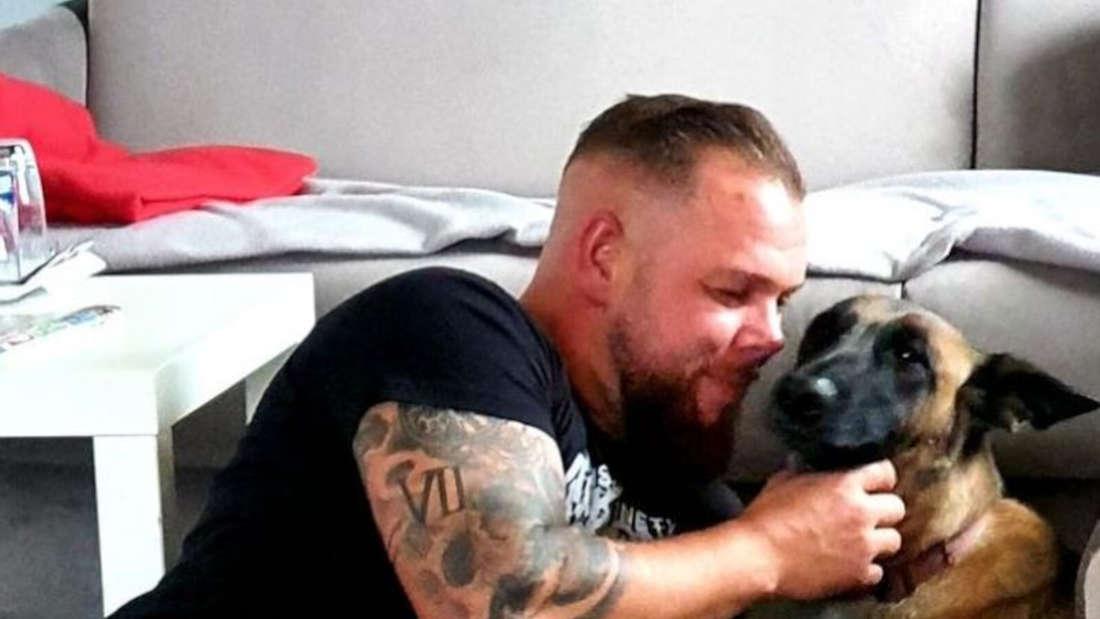 Sascha streichelt seinen Hund im Wohnzimmer