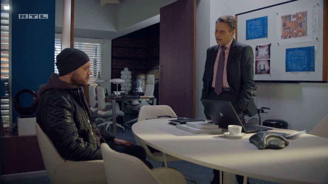 Erik sitzt in Jo Gerners Büro der steht und blickt auf Erik herab