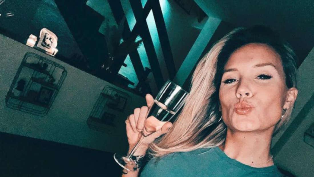 Sonia Liebing macht ein Selfie mit Sektglas und bauchfreiem Oberteil