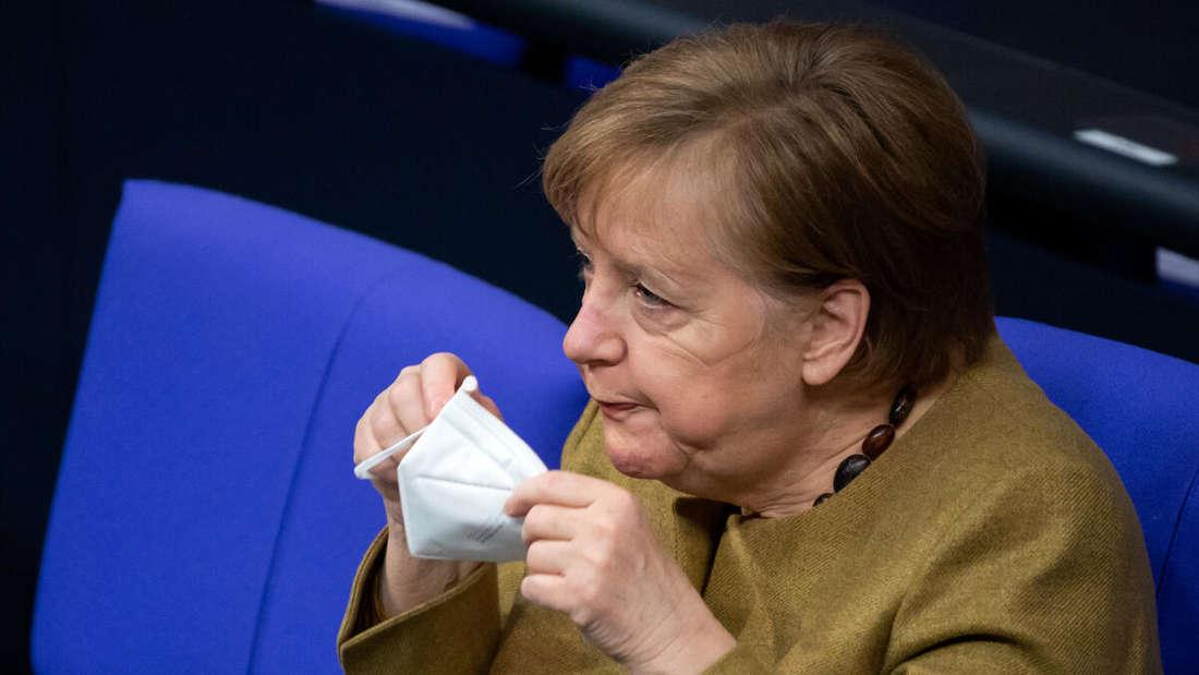 Bundeskanzlerin Angela Merkel (CDU) setzt sich bei der Plenarsitzung im Deutschen Bundestag eine FFP2-Maske auf.