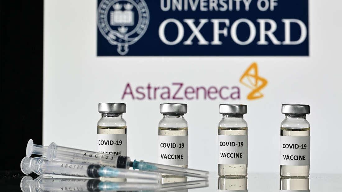 Mehrere Ampullen mit dem Vakzin von AstraZeneca stehen vor einem Schriftzug der Universität Osxford und des Pharmaunternehmens.