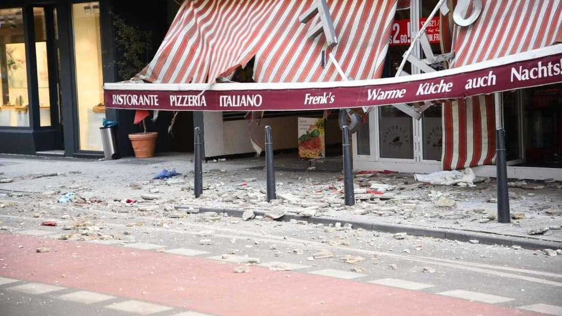 """Die herabfallenden Gebäudeteile haben die Markise des italienischen Lokals """"Frenk's"""" in Q7 durchschlagen und verteilen sich auf der Straße."""
