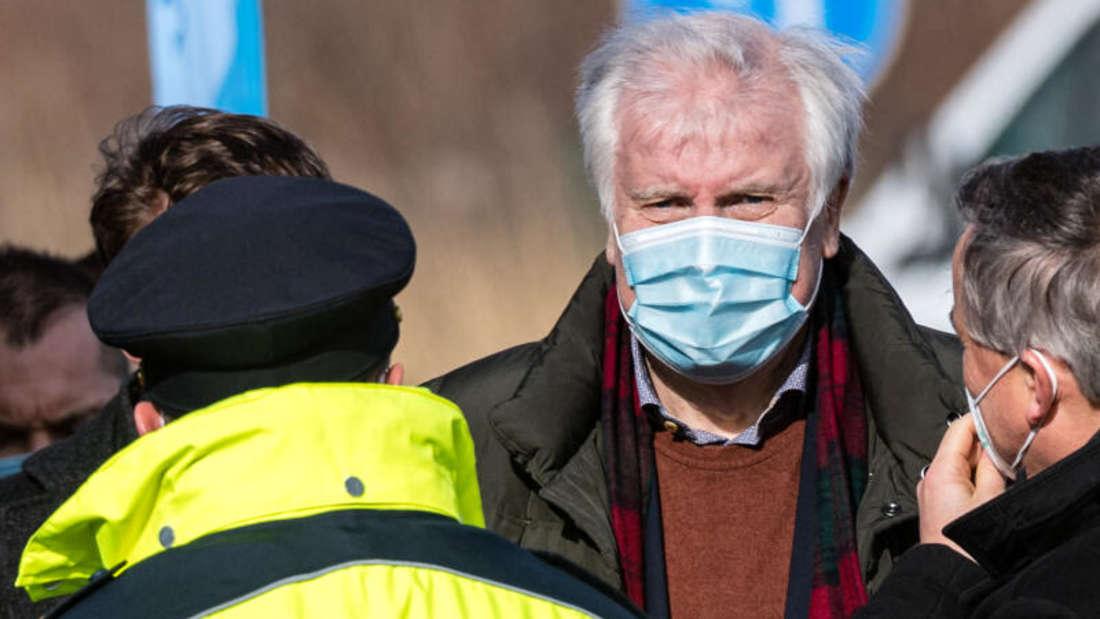 Bundesinnenminister Horst Seehofer vor einem Polizisten und weiteren Personen an der sächsisch-tschechischen Grenze