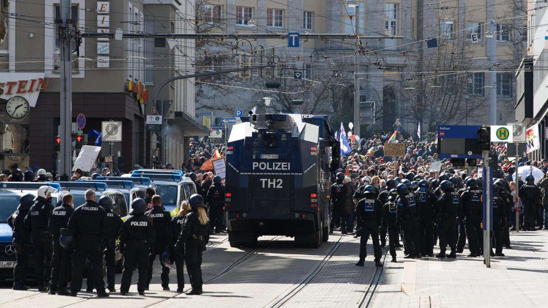 Einsatzkräfte der Polizei stehen bei einer Kundgebung unter dem Motto «Freie Bürger Kassel - Grundrechte und Demokratie» neben einem Wasserwerfer.