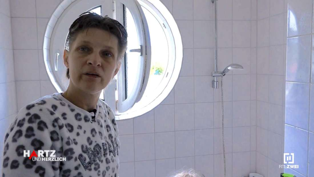 Christine steht in ihrem Bad und spricht in die Kamera
