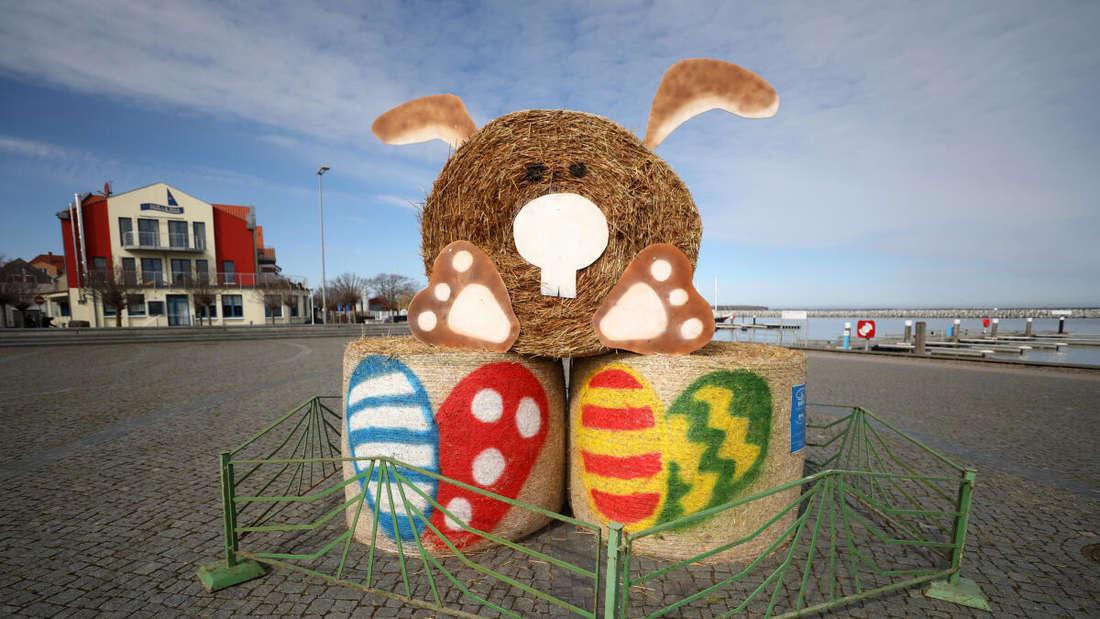 Eine Osterhasen-Skulptur aus Strohballen steht eingezäunt auf einem menschenleeren Platz am Boddenhafen des Erholungsorts an der Ostsee.