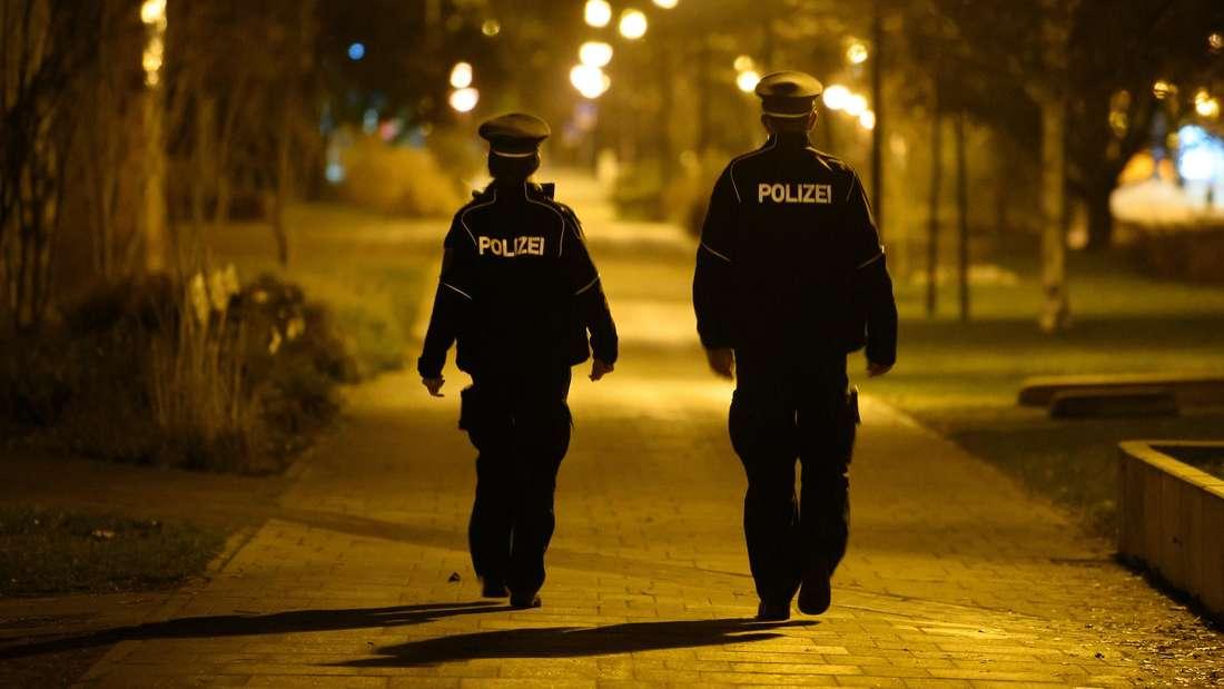 Zwei Polizeibeamte laufen in der Dunkelheit.