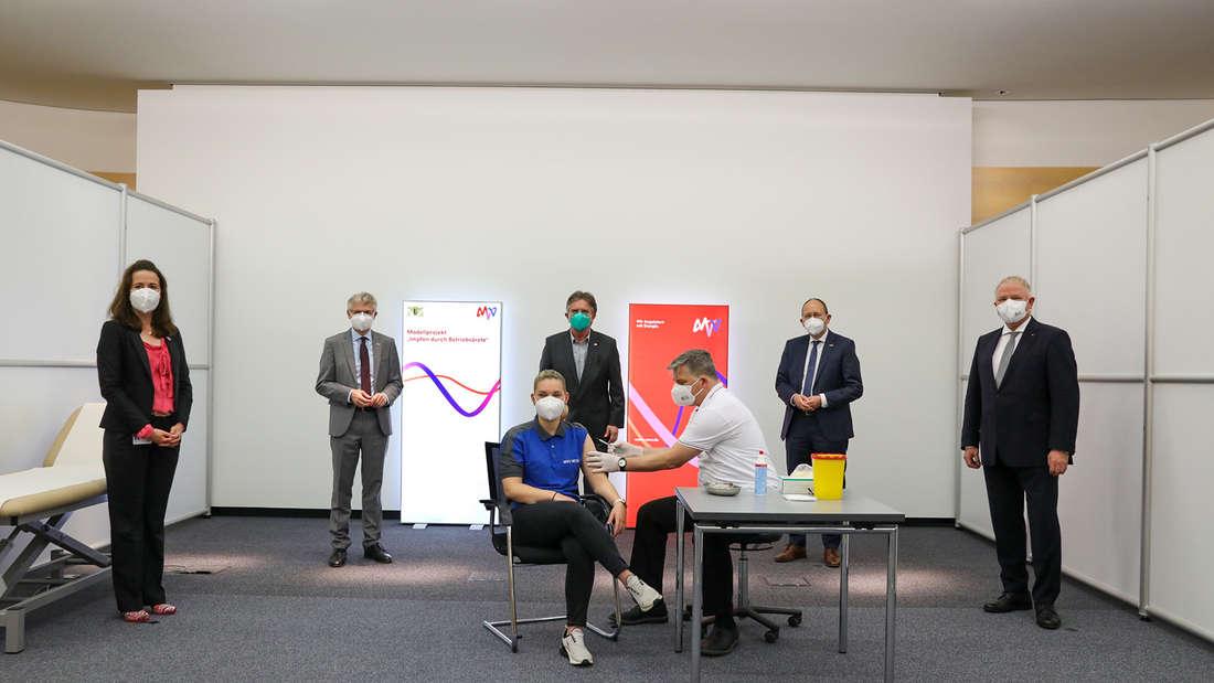 Unter den Augen des baden-württembergischen Sozialministers Manfred Lucha, MdL, (stehend Mitte), dem Ersten Bürgermeister der Stadt Mannheim, Christian Specht (2.v.r.), IHK-Präsident Manfred Schnabel (r.) sowie MVV-Vorstandschef Dr. Georg Müller und MVV-Personalvorständin Verena Amann erhält MVV-Mitarbeiterin Jennifer Mazur ihre Erstimpfung durch Betriebsarzt Dr. Claus Hölzel.