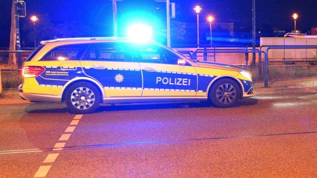 Ein Polizeiwagen steht mit angeschaltetem Blaulicht auf einer Straße.
