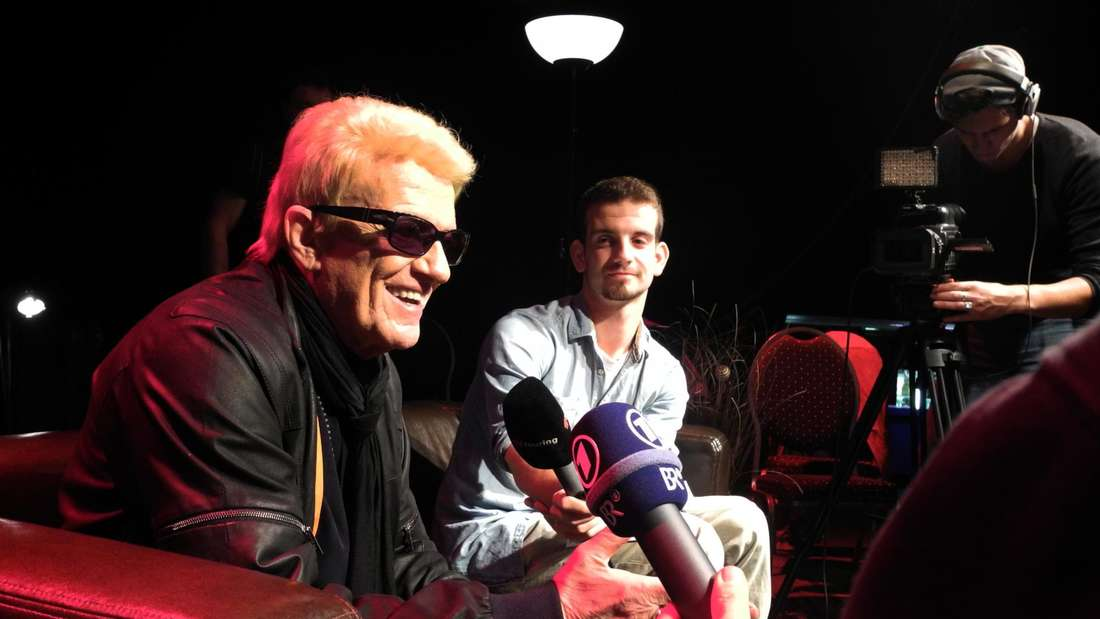 Heino sitzt auf einem Sessel und lächelt, umringt von Journalisten