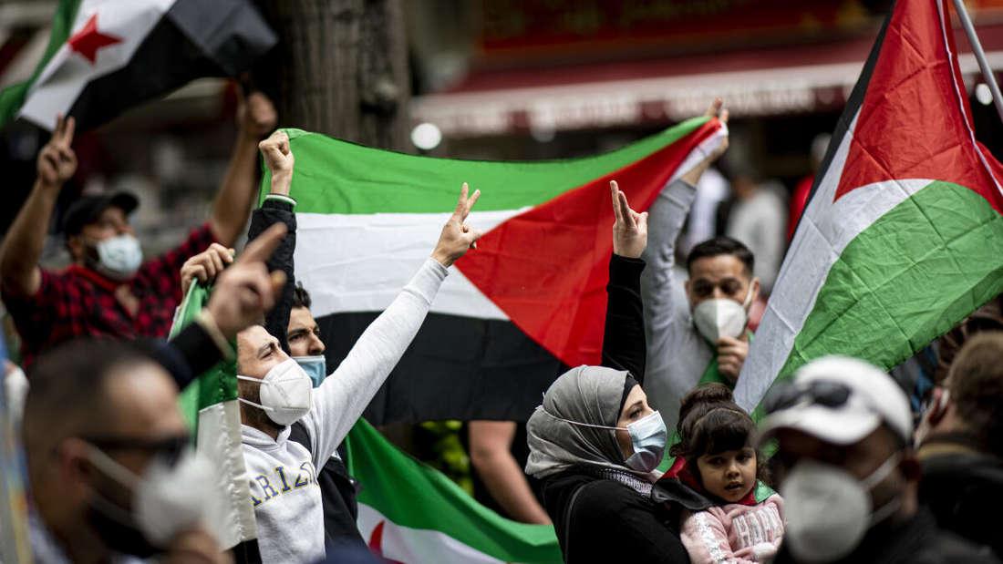 Teilnehmer der Demonstration verschiedener palästinensischer Gruppen laufen mit Palästina-Flaggen durch Neukölln.