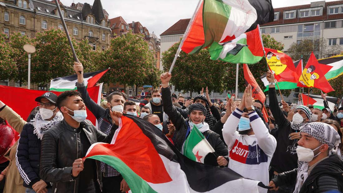 Teilnehmer bei einer pro-palästinensische Demonstration schwenken Fahnen auf dem Marienplatz in Stuttgart.