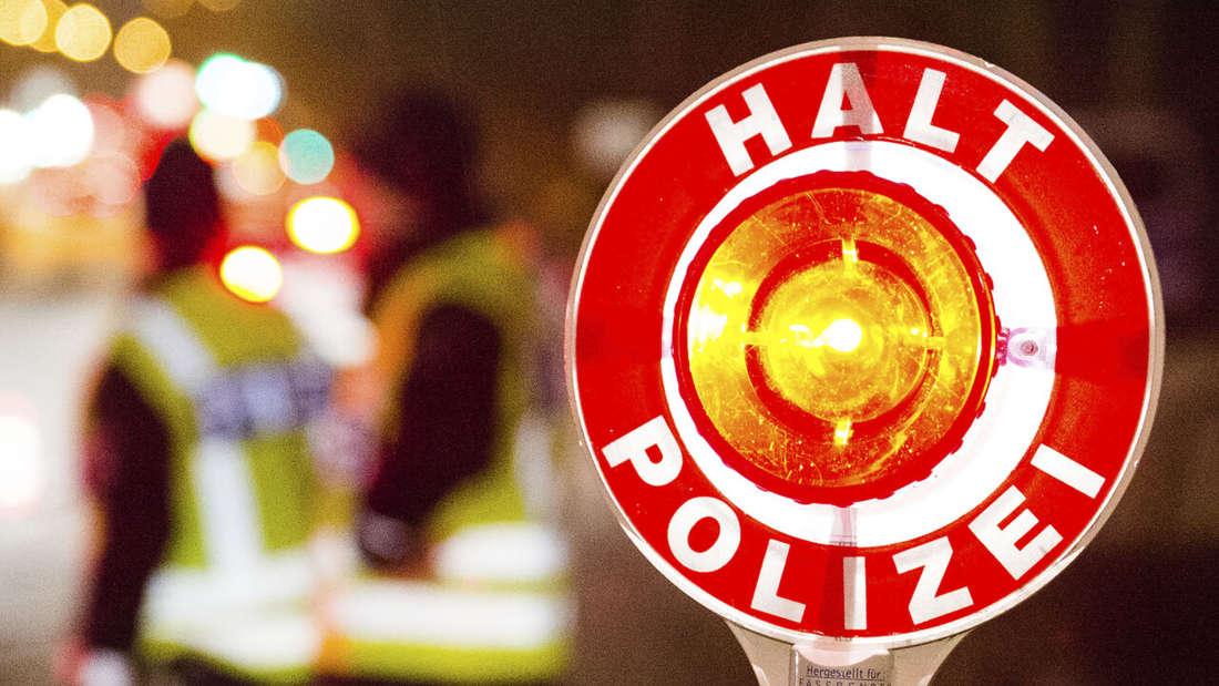 Ein Polizist hält mit einer Kelle Autofahrer bei einer nächtlichen Polizeikontrolle an. (Symbolbild)