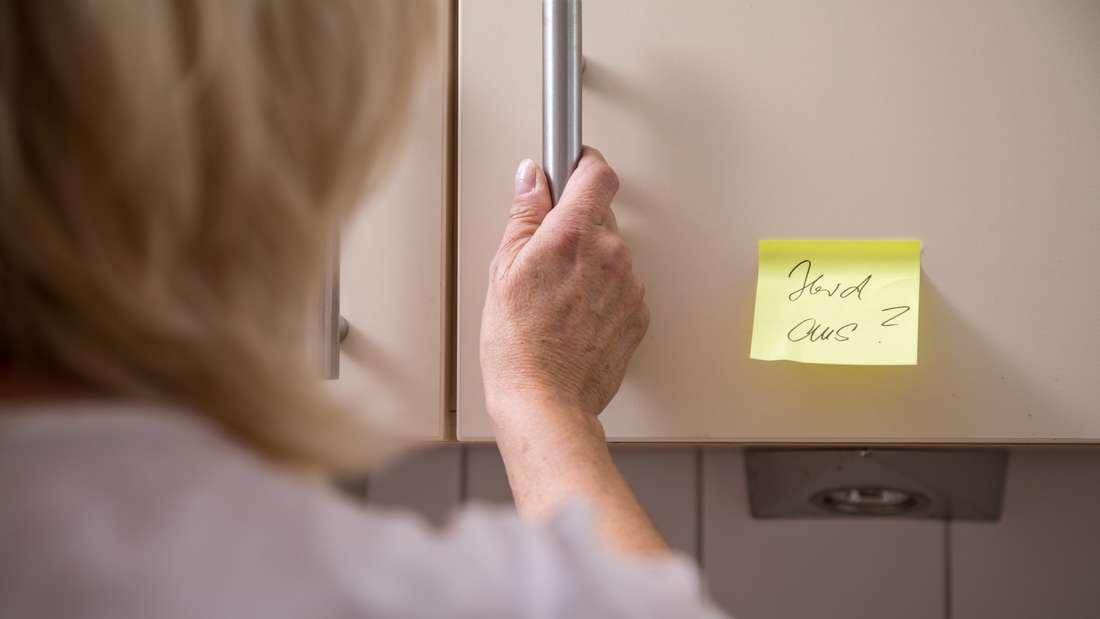 Ein Zettel, der einer an Demenz erkrankten Frau helfen soll, klebt am Küchenschrank.
