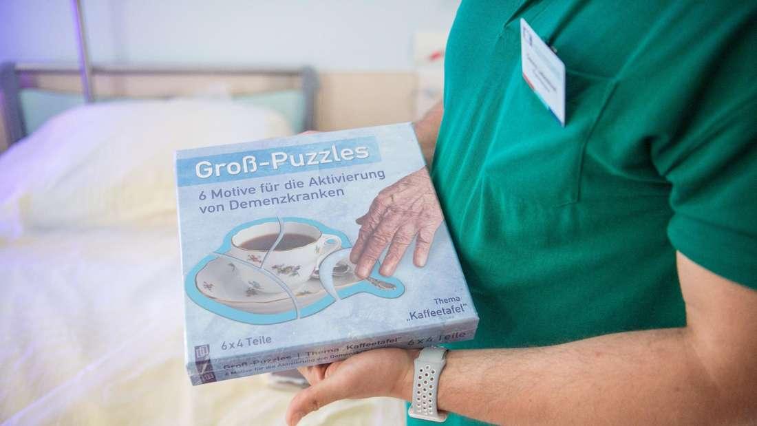Eine Pflegerin hält eine Demenz-Puzzle in den Händen