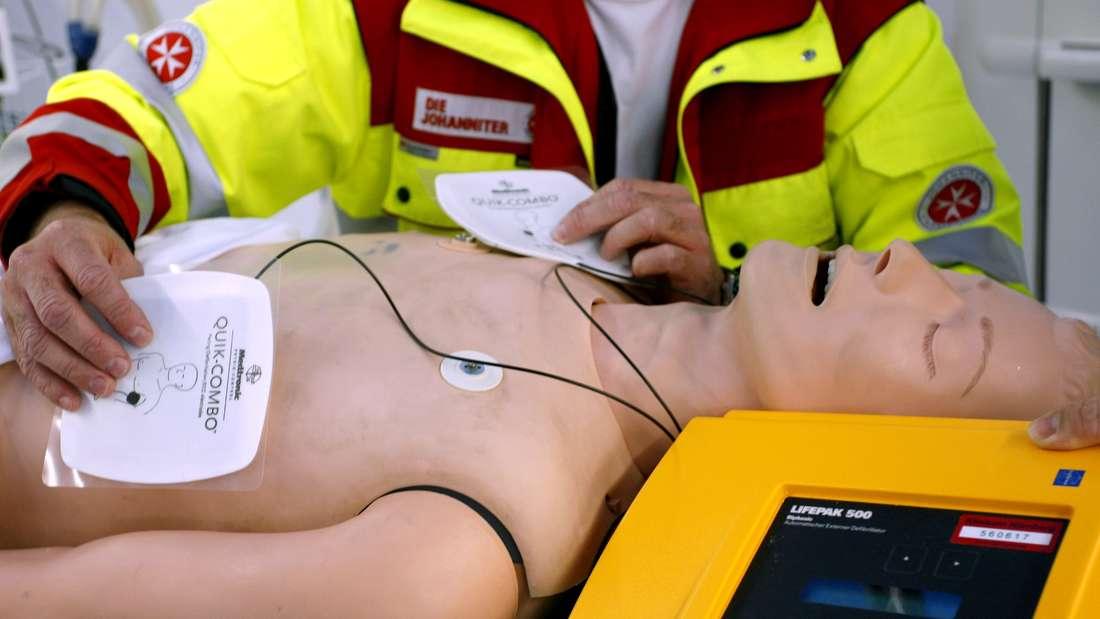 Ein Sanitäter simuliert eine Herzmassage an einer Puppe