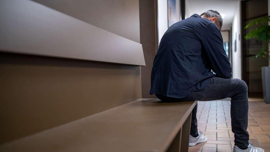 Ein Mann sitzt mit gesenktem Kopf auf einer Bank