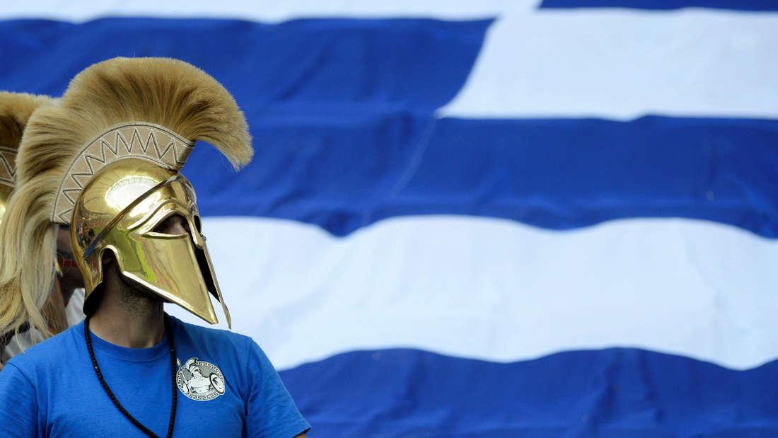 Ein Grieche trägt einen Helm vor der Flagge Griechenlands.