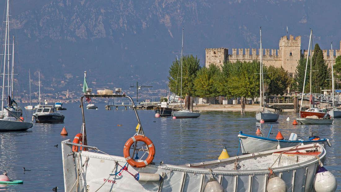 Ein Fischerboot am Gardasee, dahinter sind weitere Boote, der See und ein Schloss.