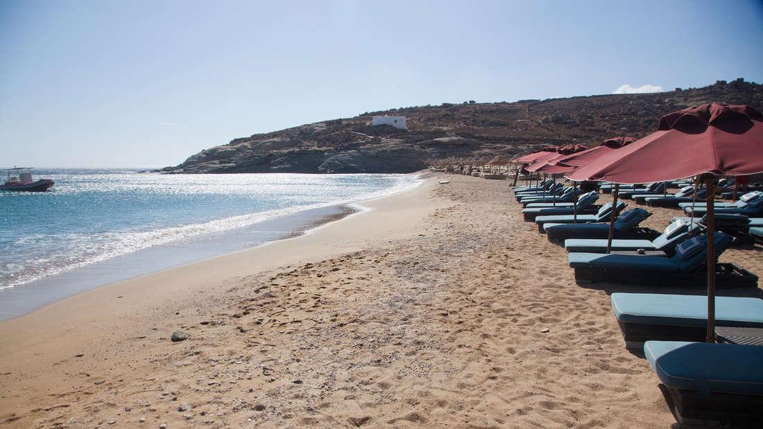 Leerer Strand mit Sonnenliegen auf Mykonos.