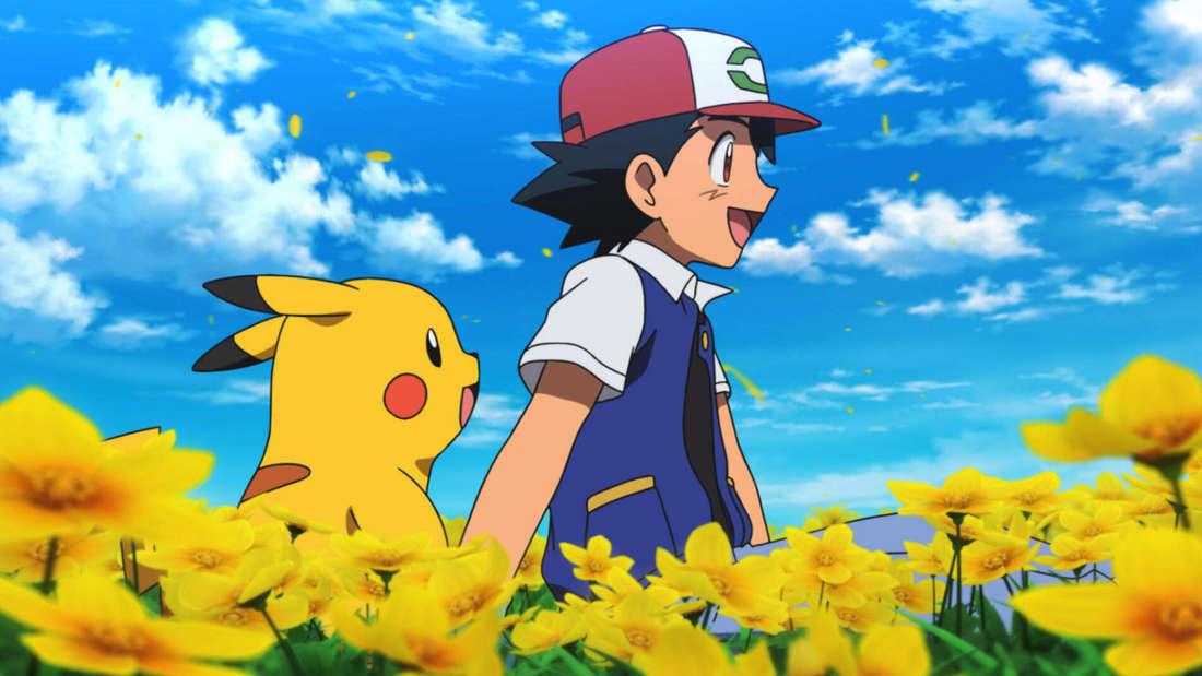 """Die Protagonisten Ash und Pikachu gehen in """"Pokémon – Der Film: Du bist dran!"""" über eine Blumenwiese."""