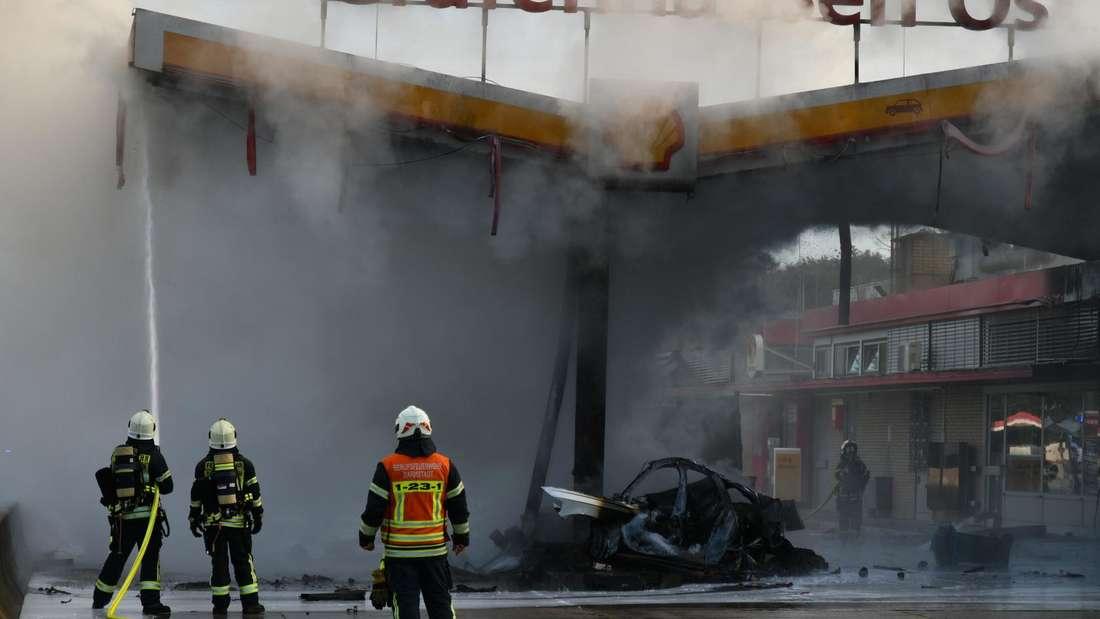 Feuerwehrleute kämpfen an der Tankstelle der Raststätte Gräfenhausen Ost gegen die Flammen.