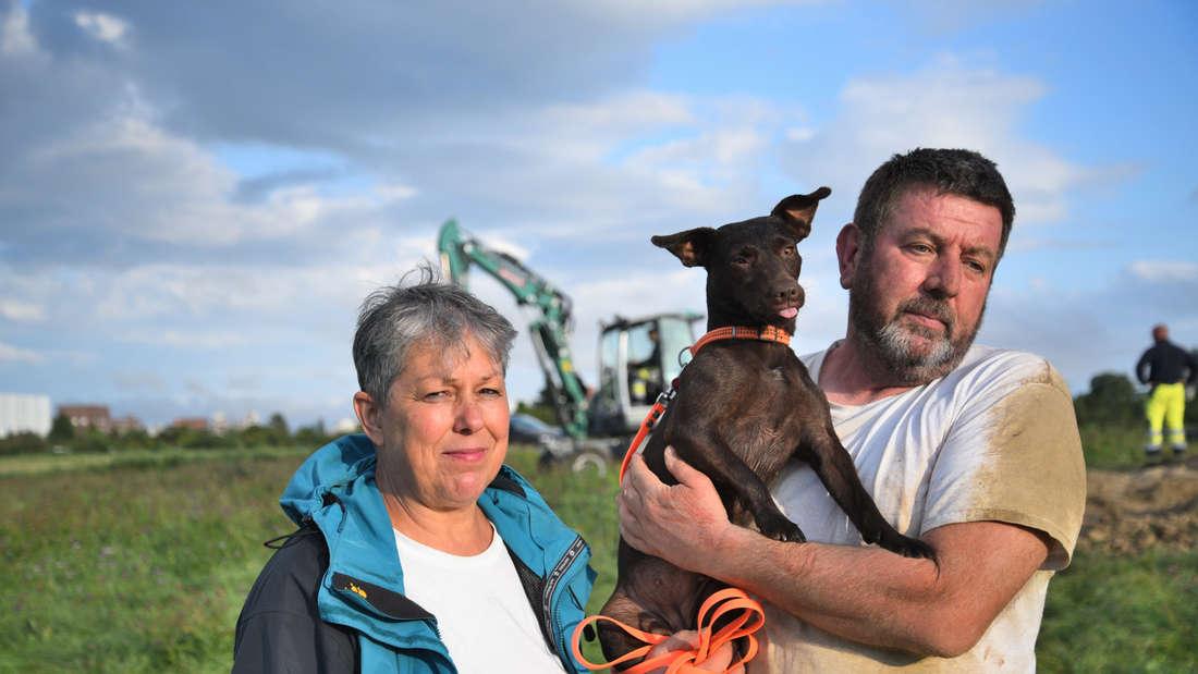 Die Besitzer halten den Hund auf dem Arm.