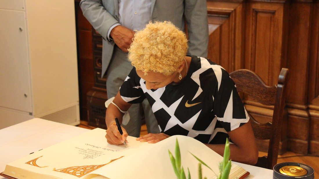 Malaika Mihambo unterschreibt im Goldenen Buch der Stadt Heidelberg.