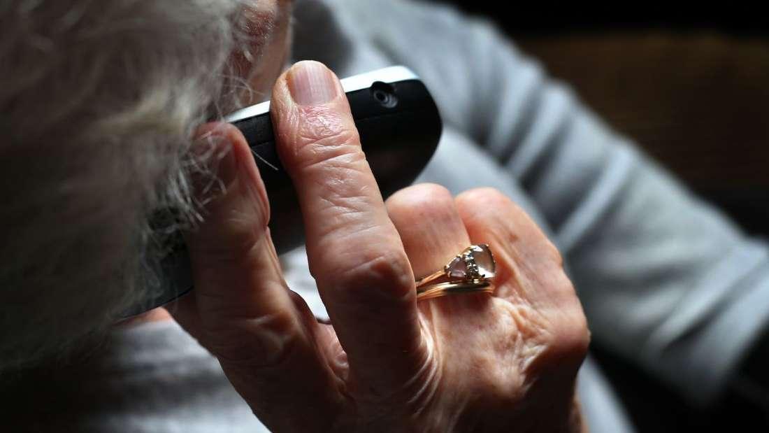 Eine ältere Frau telefoniert mit einem schnurlosen Festnetztelefon.