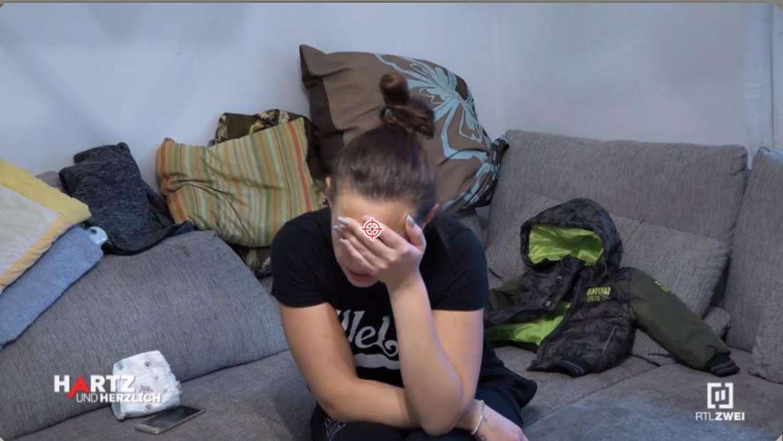 Janine sitzt auf dem Sofa uns fasst sich an den Kopf